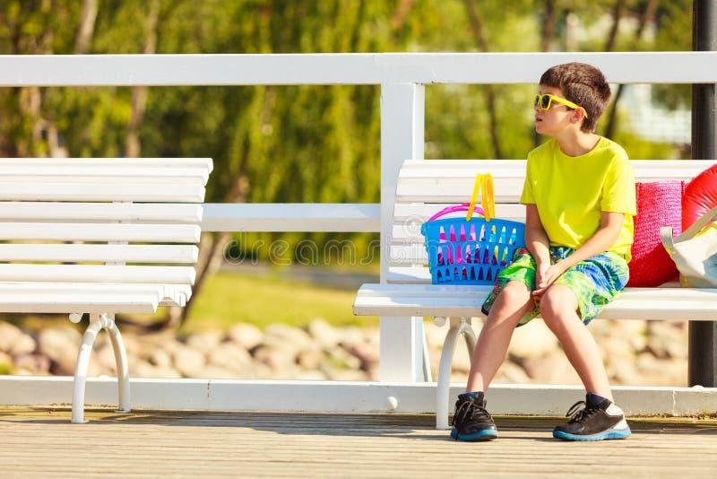 男孩坐与玩具的长凳 库存照片