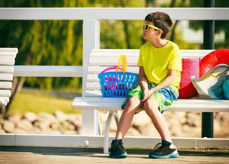 男孩坐与玩具的长凳 库存图片