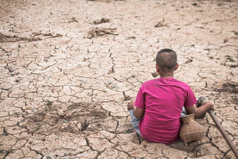 男孩坐充满绝望的贫瘠地面 图库摄影