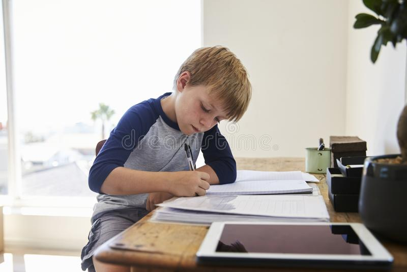 男孩坐在书桌在有做家庭作业的数字式片剂的卧室 库存图片