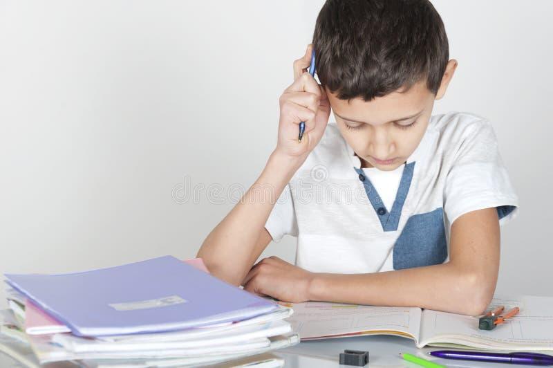 男孩坐在做他的家庭作业的书桌 图库摄影