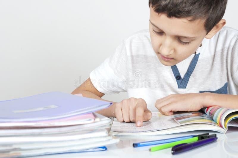男孩坐在做他的家庭作业的书桌 免版税库存照片