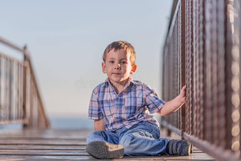 男孩坐在水池的桥梁在日落 库存照片