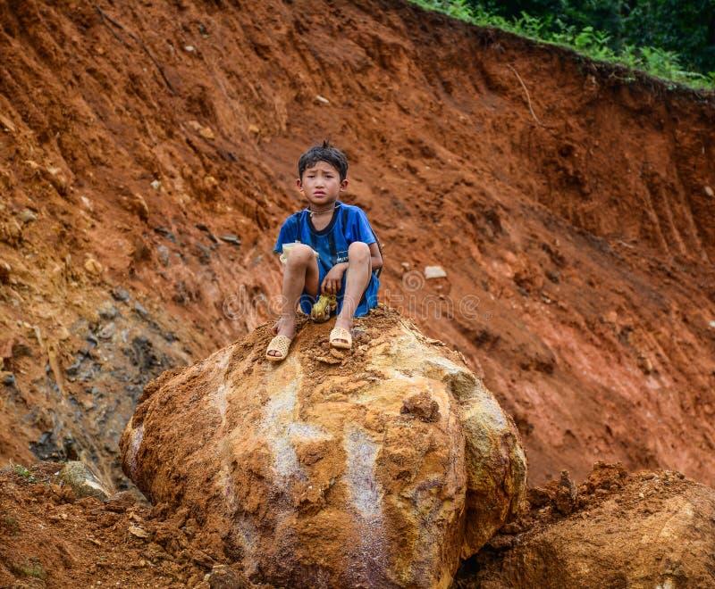 男孩坐在Sa Pa的岩石,越南 图库摄影