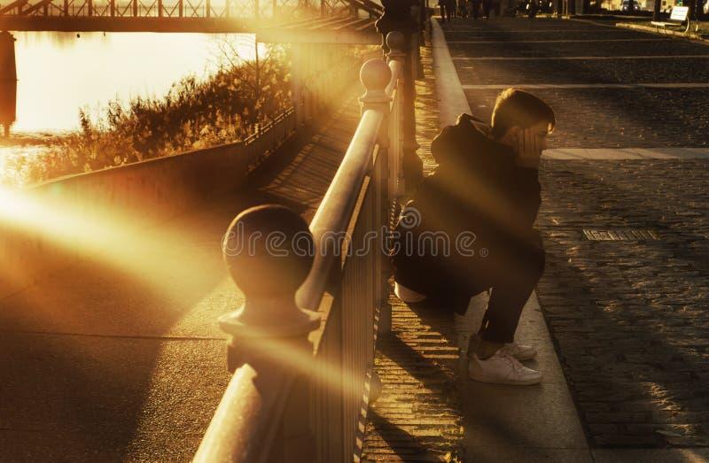 男孩坐城市地板在与光束的日落 免版税库存图片
