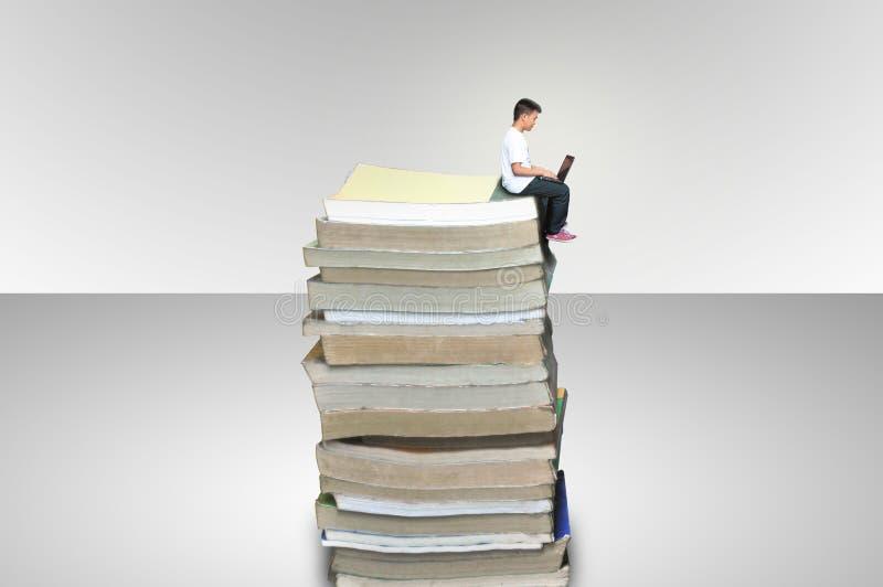 男孩坐堆书 免版税图库摄影