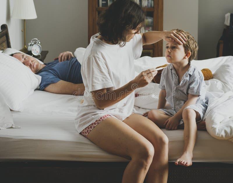 男孩坐床和他的检查温度的妈妈 免版税库存图片