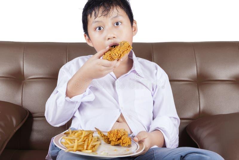 男孩坐沙发,当吃炸鸡时 免版税库存图片