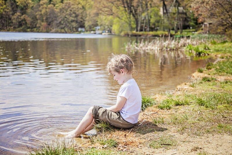 男孩坐湖岸  库存图片