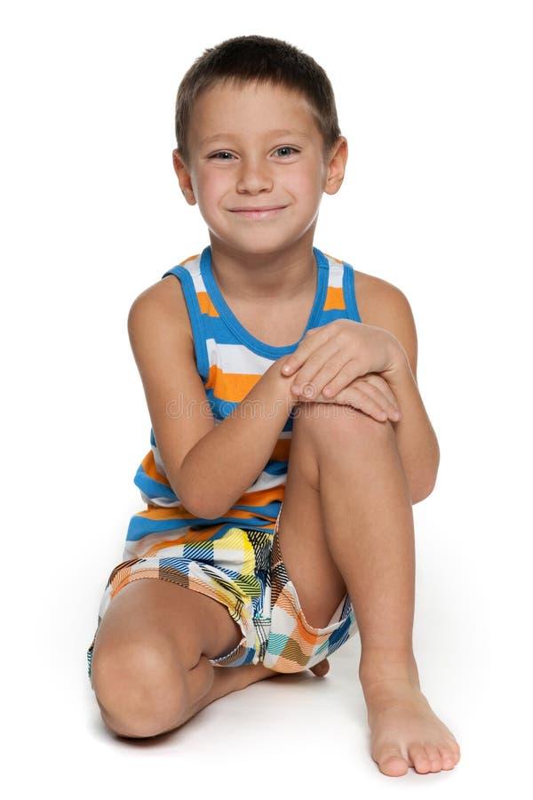 年轻男孩坐白色背景 库存图片