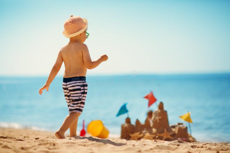 男孩坐的微笑对海滩 库存图片