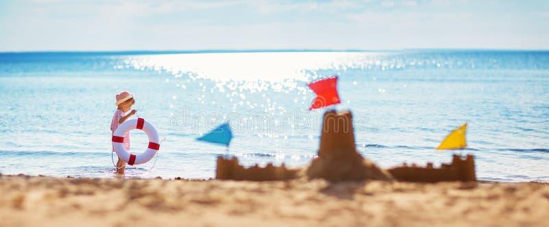 男孩坐的微笑对海滩 免版税库存照片