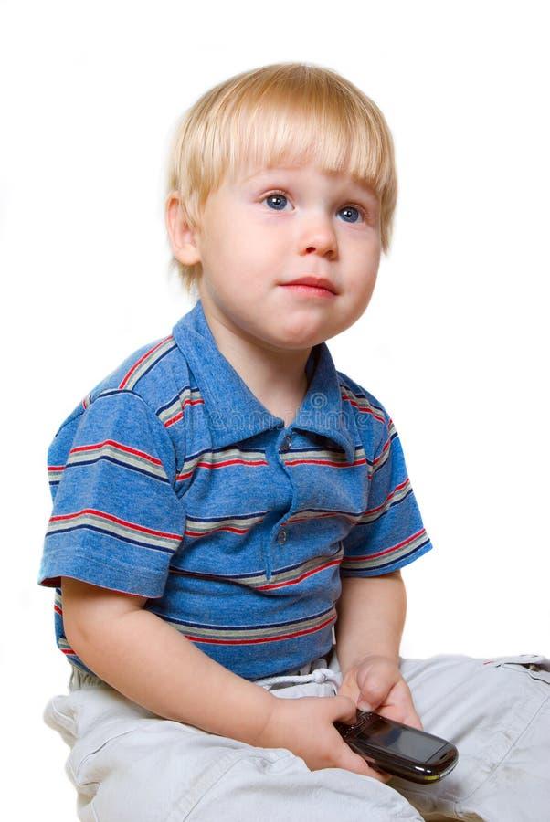 男孩坐的电话 库存照片