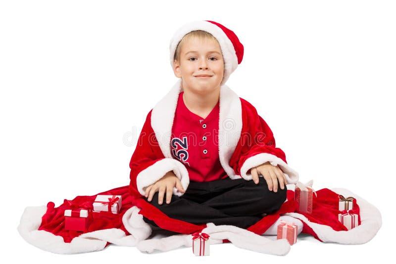 男孩坐穿戴作为圣诞老人隔绝了 免版税库存图片