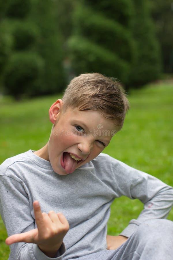 男孩坐绿色草坪并且微笑 免版税库存图片