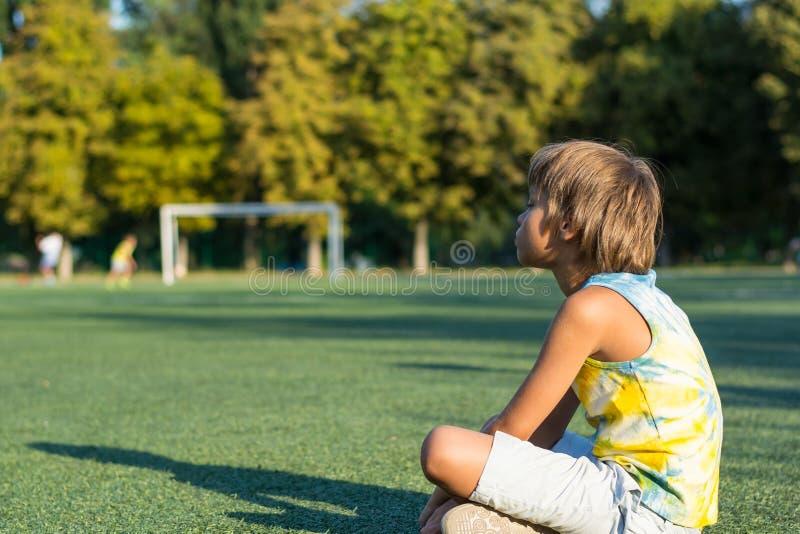 男孩坐草在体育场和手表的边缘 免版税库存照片