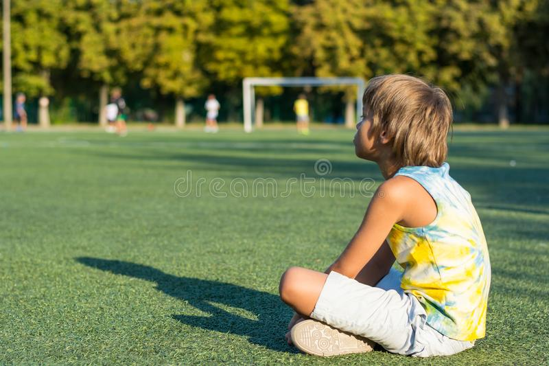男孩坐草在学校的体育场的边缘 库存图片