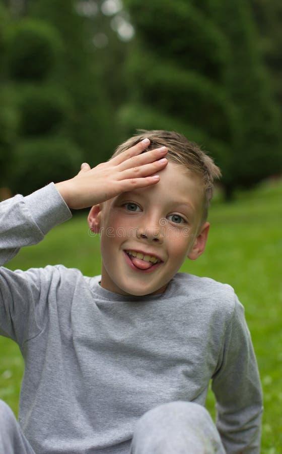男孩坐草坪并且为照相机微笑 免版税图库摄影