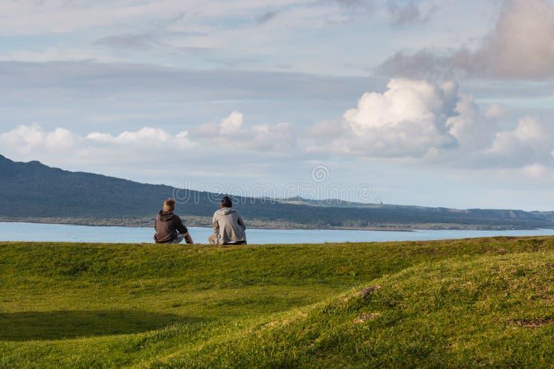 男孩坐草观看的云彩 图库摄影