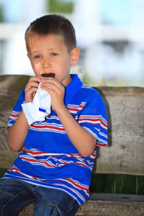 男孩坐长凳在吃巧克力的公园 免版税库存图片