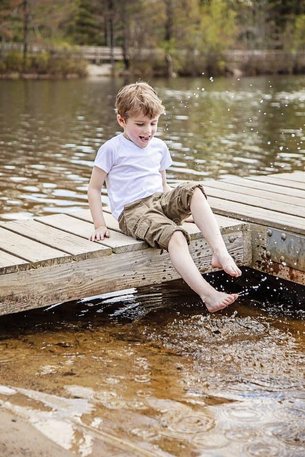 男孩坐飞溅水的船坞在湖 库存图片