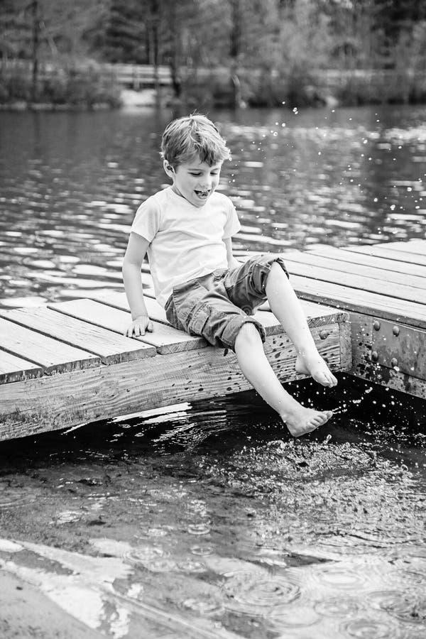 男孩坐飞溅水的船坞在湖 免版税图库摄影