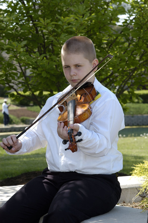 男孩外部使用的坐的中提琴 库存照片