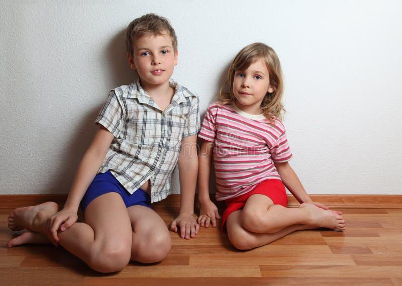 男孩女孩一点坐的微笑周道 免版税库存图片