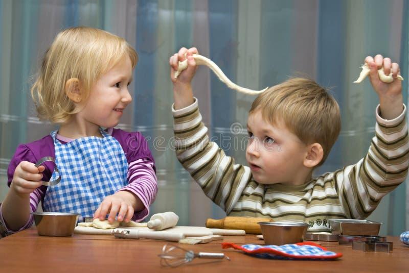 男孩女孩小帮助的厨房 库存图片