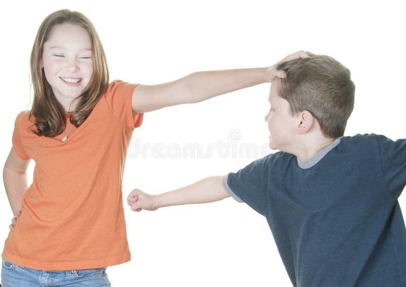 男孩女孩戏弄的年轻人 免版税库存图片