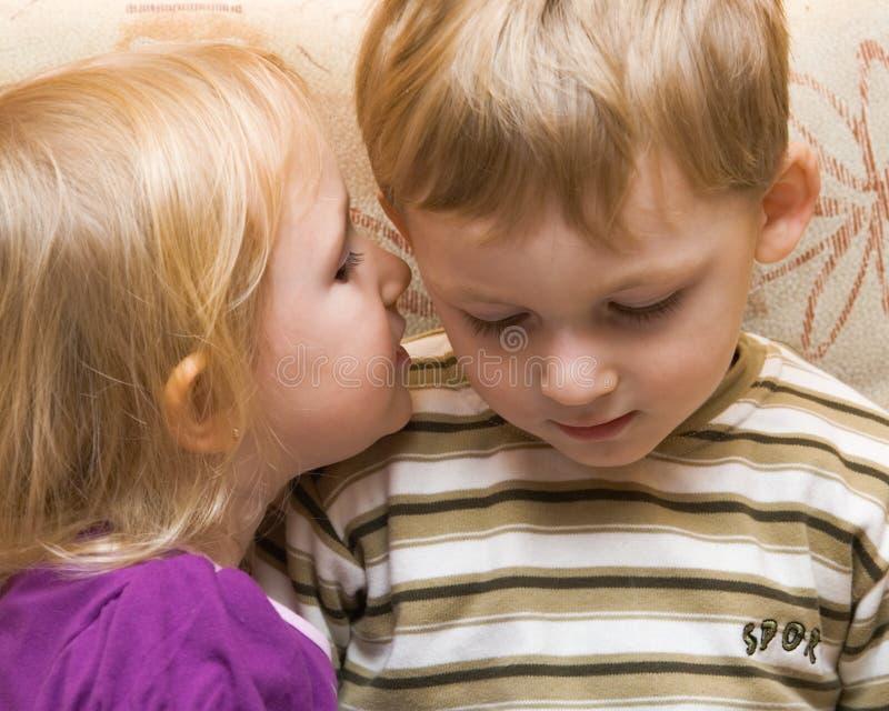 男孩女孩耳语年轻人 免版税库存照片
