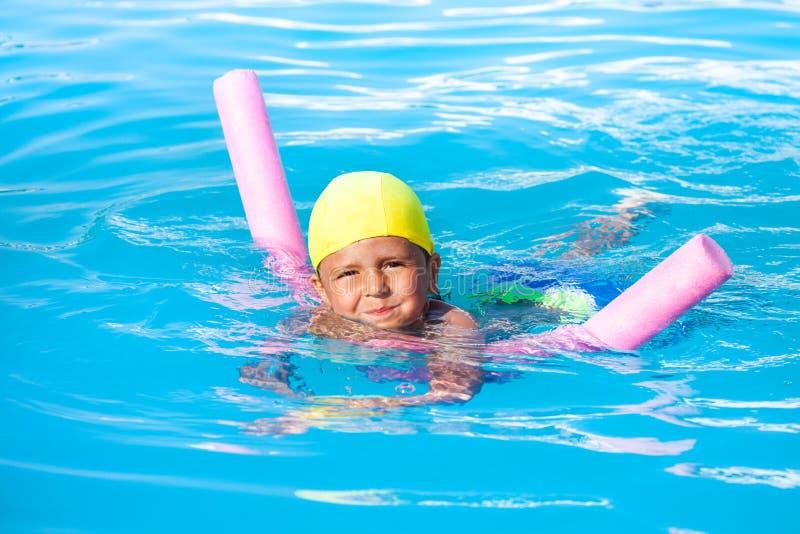 男孩学会单独游泳用水池面条 免版税库存图片