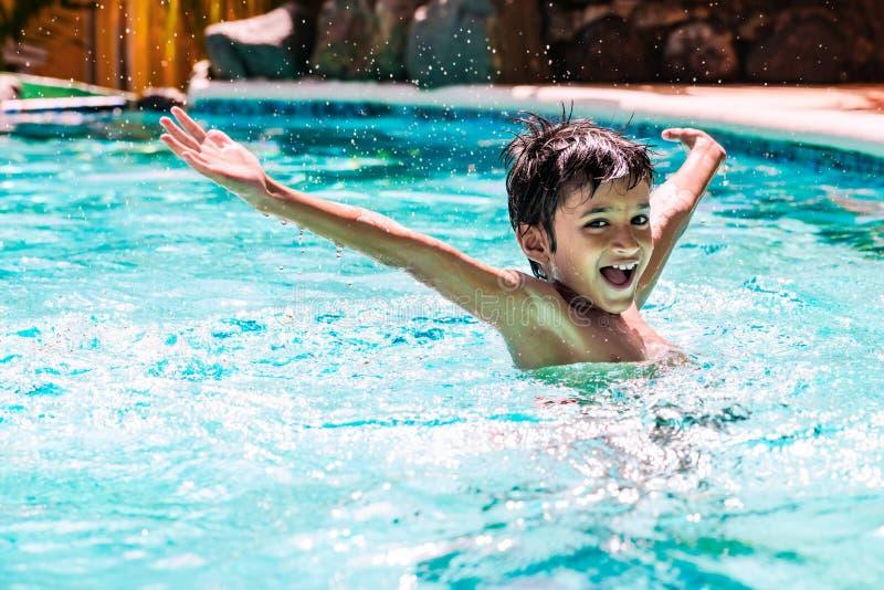 年轻男孩孩子孩子飞溅在游泳池的八岁有乐趣娱乐活动开放胳膊 库存照片