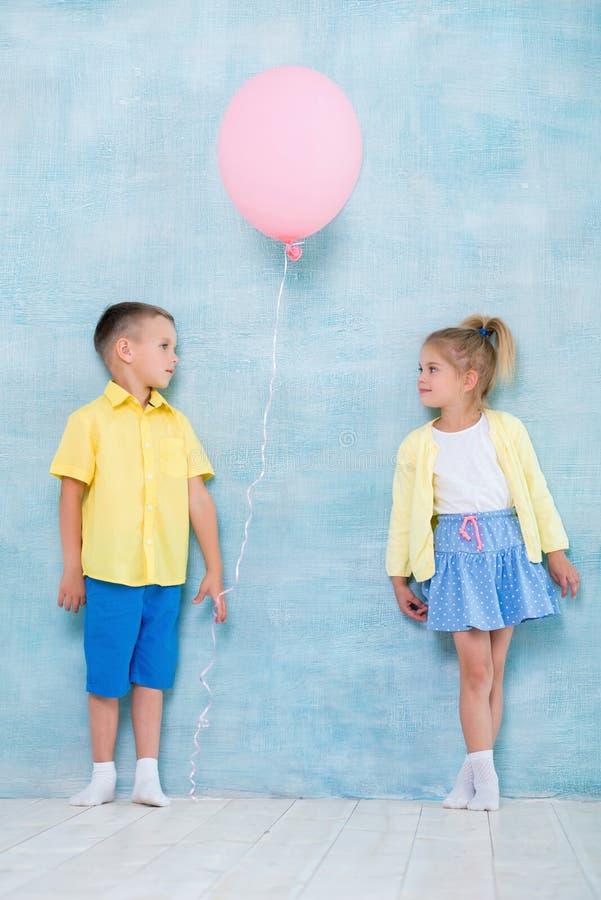 男孩孩子给一个气球女孩 注意、同情和求爱的标志 免版税库存照片