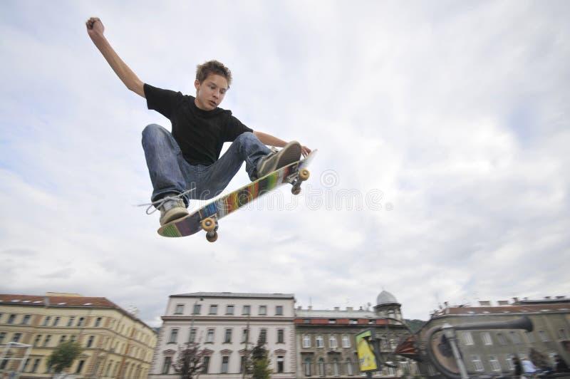 男孩实践的踩滑板 库存图片