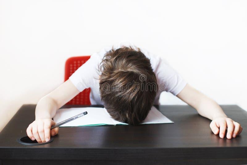 男孩对做家庭作业是疲乏 孩子坐并且家庭作业 免版税图库摄影