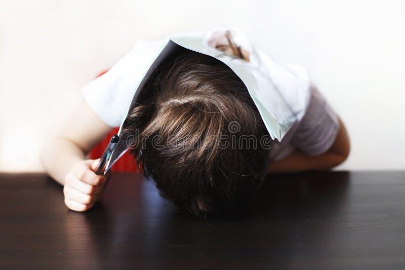 男孩对做家庭作业是疲乏 孩子坐并且家庭作业 库存照片