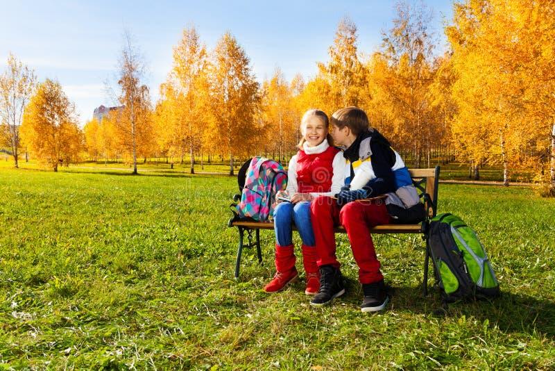 男孩对女孩耳朵耳语 免版税库存图片