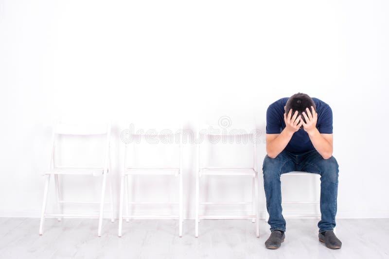 男孩少年坐与下来他的头的一把椅子,和拿着它用两只手 他是有些生气和情感地弄翻 免版税库存图片
