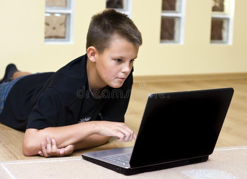 男孩少年楼层的膝上型计算机 库存图片
