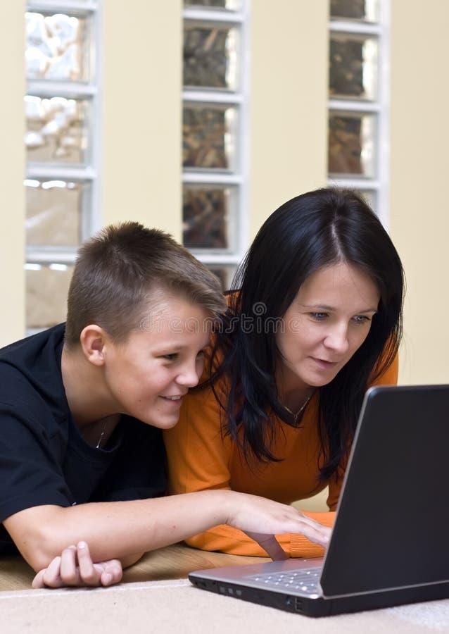 男孩少年膝上型计算机的母亲 库存图片