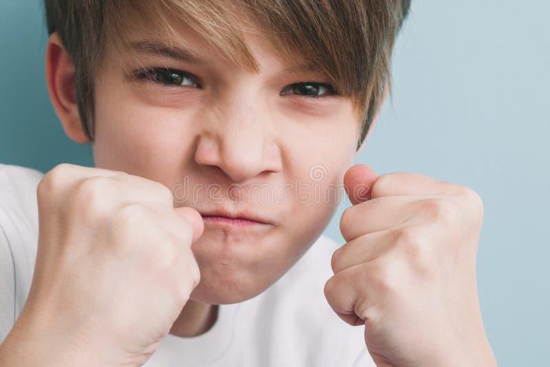 男孩尖叫和开玩笑地威胁与他的在战斗的姿态的拳头 图库摄影