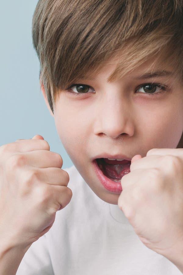 男孩尖叫和开玩笑地威胁与他的拳头 免版税库存图片