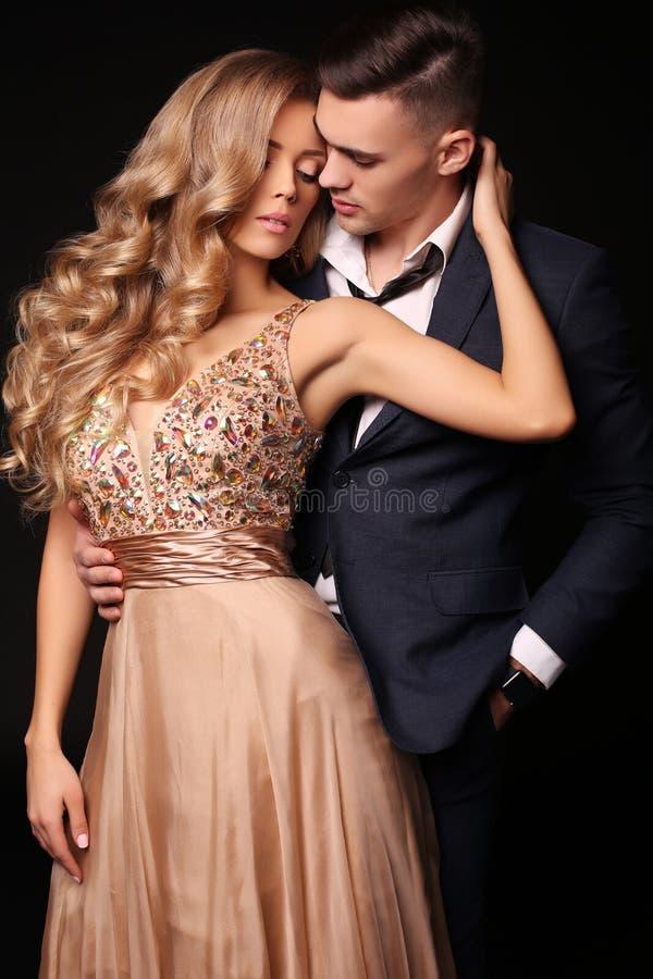 男孩庭院女孩亲吻的爱情小说 美好的性感的夫妇 华美的白肤金发的妇女和英俊的人 免版税库存图片
