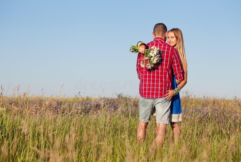 男孩庭院女孩亲吻的爱情小说 走在草甸的美好的年轻夫妇,室外 库存照片