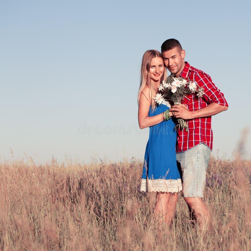 男孩庭院女孩亲吻的爱情小说 走在草甸的美好的年轻夫妇,室外 免版税库存图片