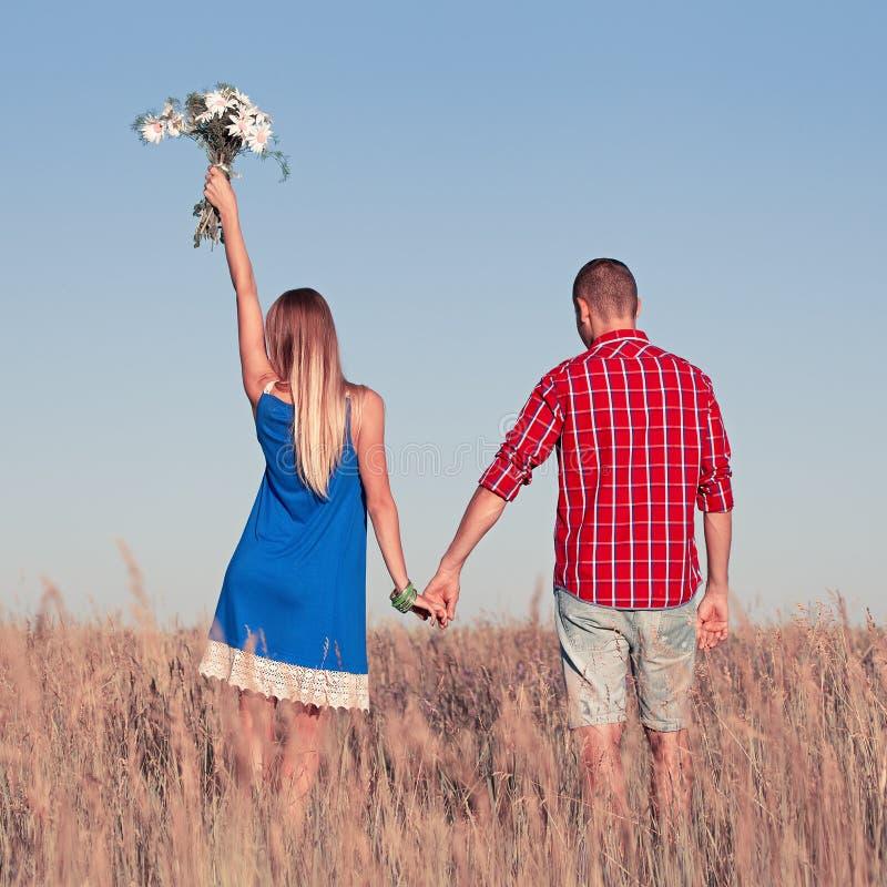 男孩庭院女孩亲吻的爱情小说 走在草甸的美好的年轻夫妇,室外 免版税库存照片