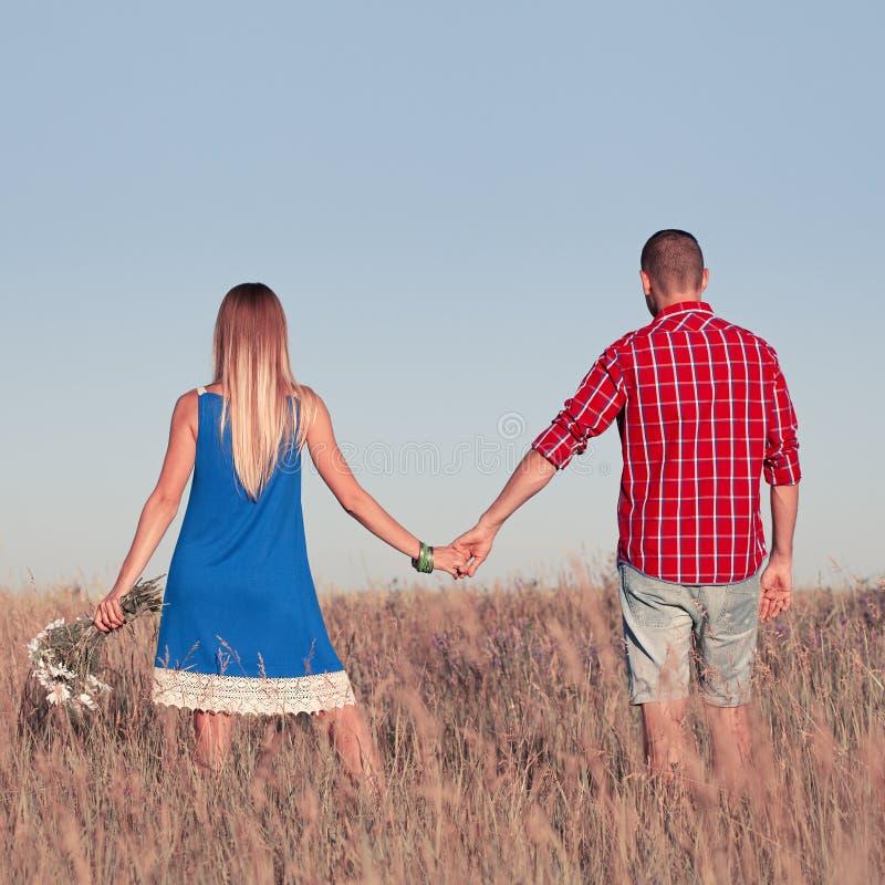 男孩庭院女孩亲吻的爱情小说 走在草甸的美好的年轻夫妇,室外 图库摄影
