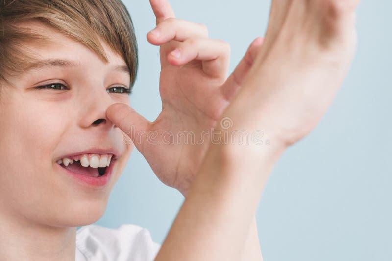 男孩开玩笑地显示他与他的手指棕榈的长的鼻子对照相机 库存图片