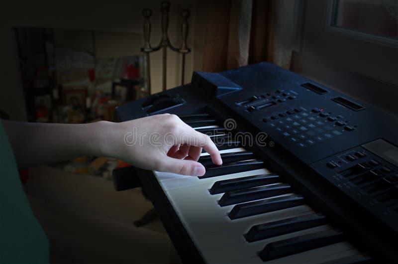 男孩弹电子钢琴 免版税库存照片